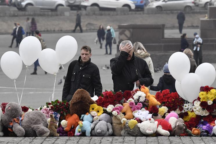 """VLADIVOSTOK, RUSSIA - MARCH 28, 2018: People bring toys and flowers to a monument to the Fighters for Soviet Power in the Far East in Vladivostok's Central Square as they mourn the victims of the March 25 fire at the Zimnyaya Vishnya [Winter Cherry] shopping centre killing at least 64, many of them children, in Kemerovo. Yuri Smityuk/TASS Ðîññèÿ. Âëàäèâîñòîê. 28 ìàðòà 2018. Ñòèõèéíûé ìåìîðèàë ó ïàìÿòíèêà Áîðöàì çà âëàñòü Ñîâåòîâ â ïàìÿòü î æåðòâàõ ïîæàðà 25 ìàðòà 2018 ãîäà â òîðãîâîì öåíòðå """"Çèìíÿÿ âèøíÿ"""" â Êåìåðîâå, ãäå ïî îôèöèàëüíûì äàííûì ïîãèáëè áîëåå 60 ÷åëîâåê. 28 ìàðòà îáúÿâëåí íàöèîíàëüíûé òðàóð ïî ïîãèáøèì. Þðèé Ñìèòþê/ÒÀÑÑ"""